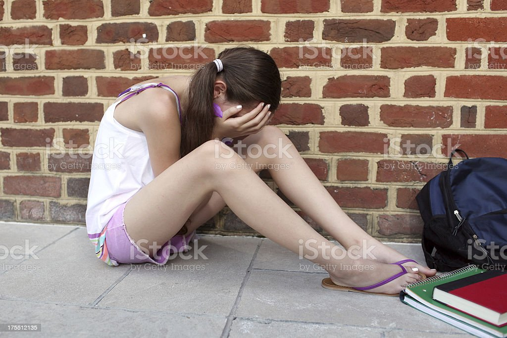 Young girl sitting on the floor upset after being bullied royalty-free stock photo