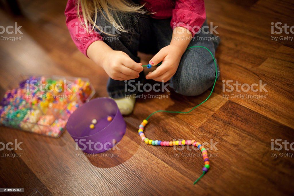 Young Girl Sitting on Wood Floor and Stringing Beads stock photo