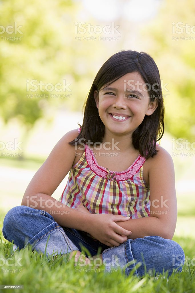 Young girl sitting outdoors smiling royalty-free stock photo