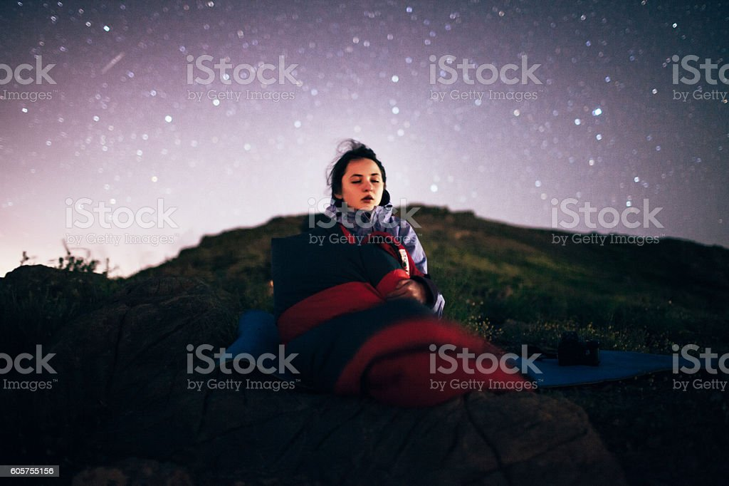 Young girl sitting under the starry sky stock photo