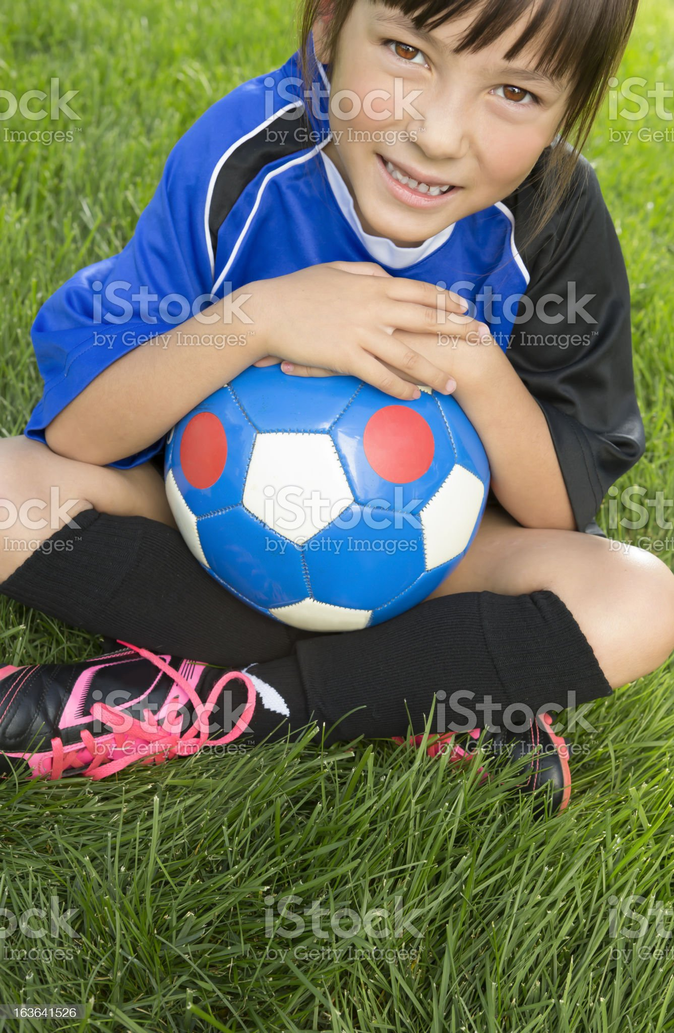 Young girl sitting with her soccer ball royalty-free stock photo