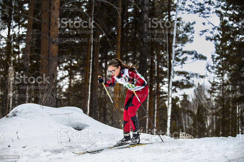 young girl skier athlete coming down mountain on skis stock photo