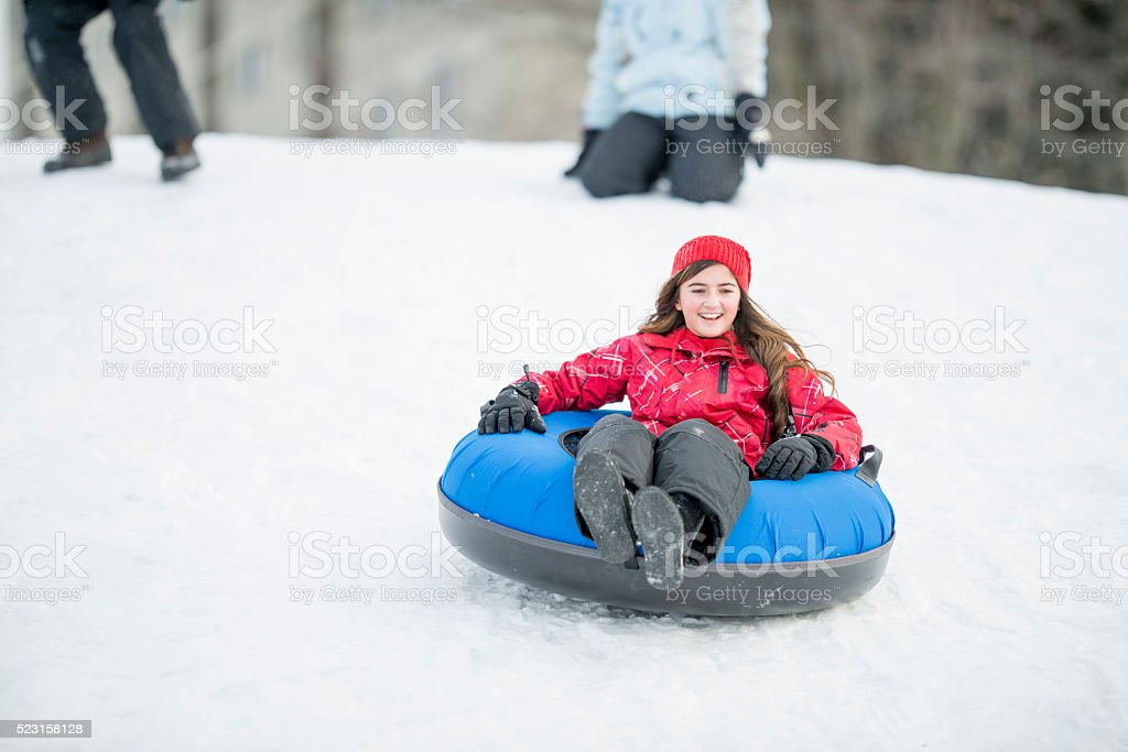 Young Girl Sledding Down a Hill stock photo