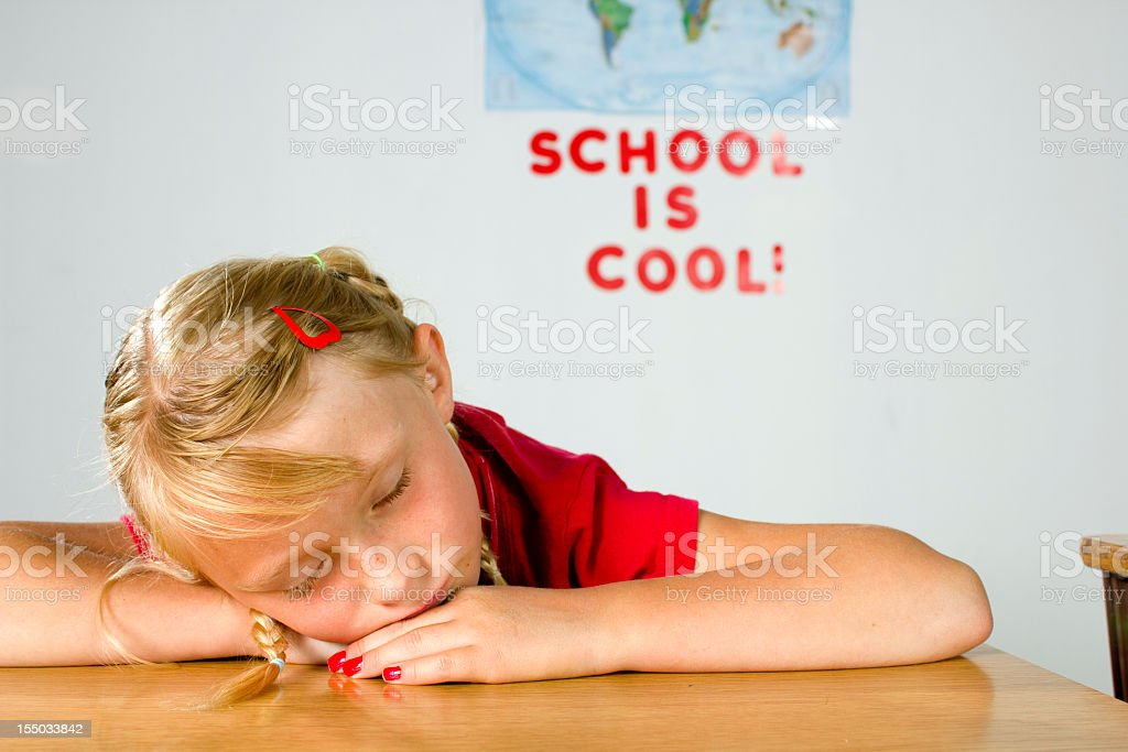 Young girl sleeping in class stock photo