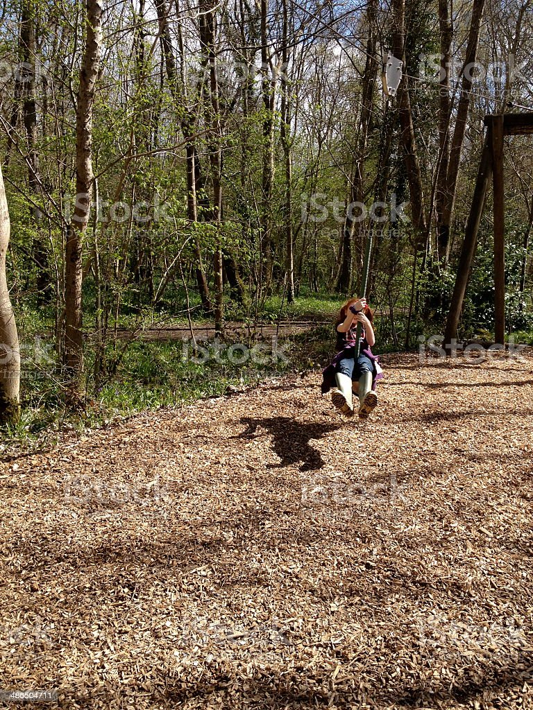Young girl sliding down zip line / wire in woodland playground stock photo