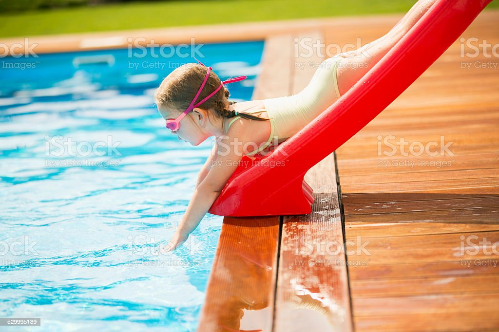 Young girl sliding into swimming pool stock photo