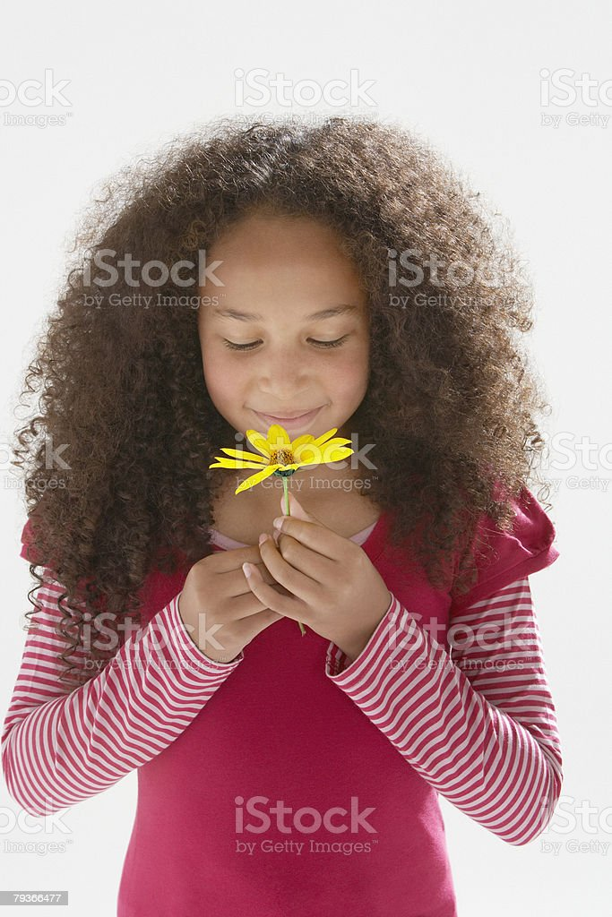 Young girl smelling flower indoors stock photo