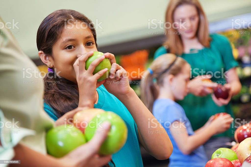 Young girl smelling green apple while shopping at grocery store royalty-free stock photo