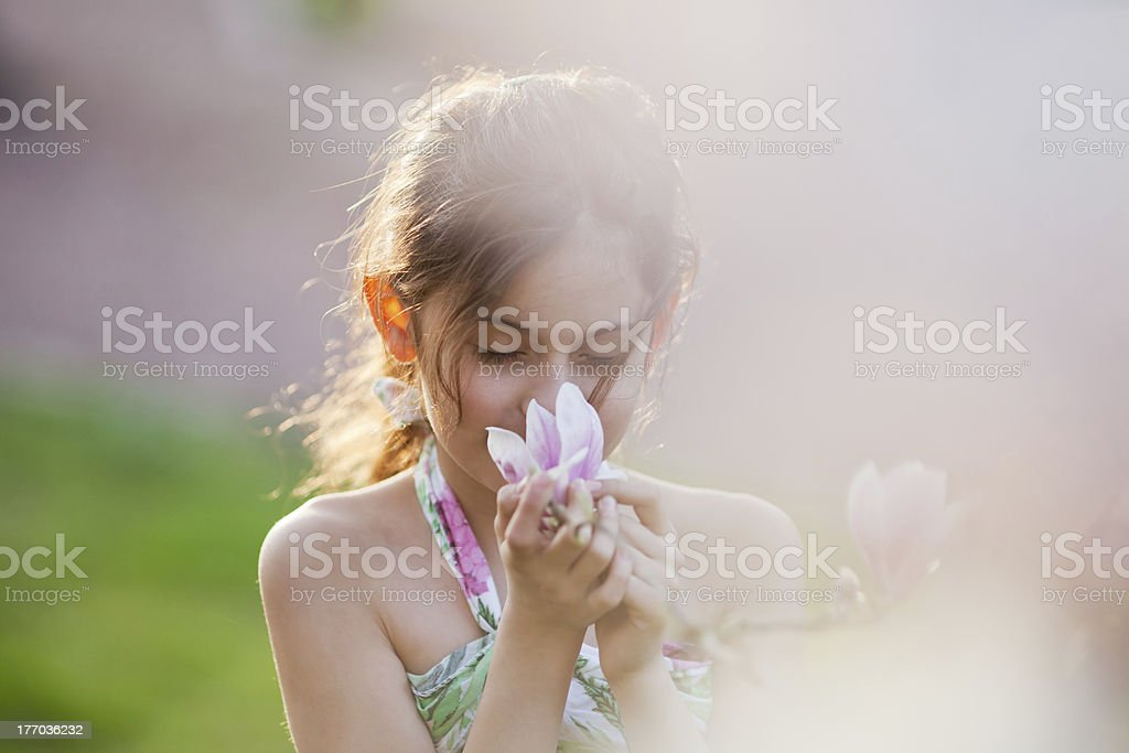 young girl smells at a blossom stock photo