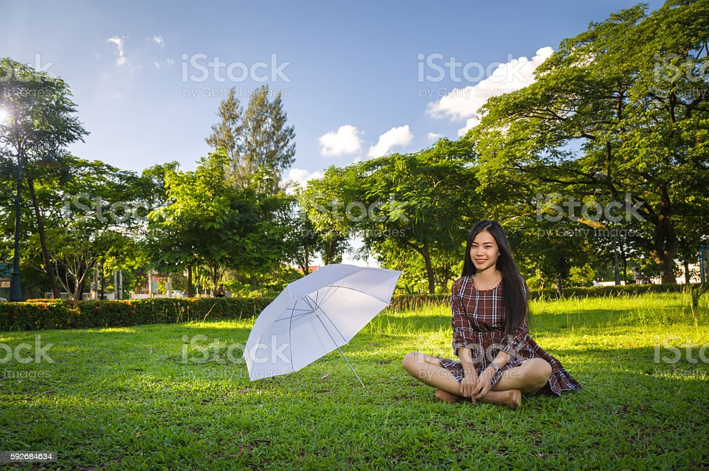 young girl smiling sitting with white umbrella stock photo