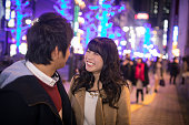 Young girl smiling to boyfriend in city