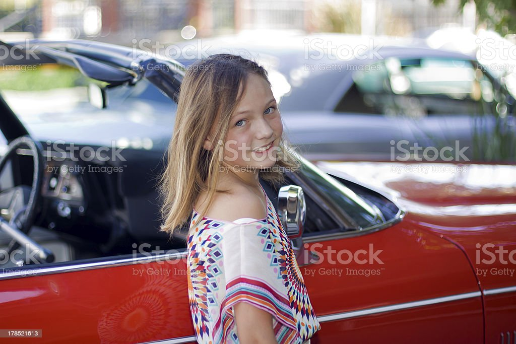 Young Girl Smiling With A Antique Convertible royalty-free stock photo