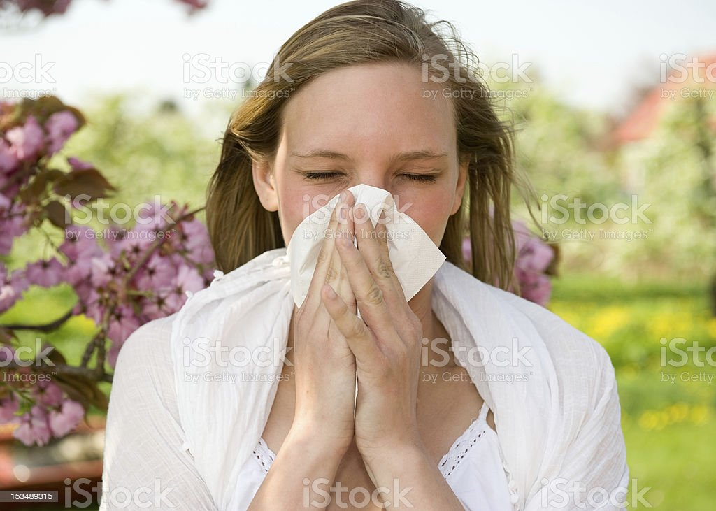A young girl sneezing into a tissue stock photo