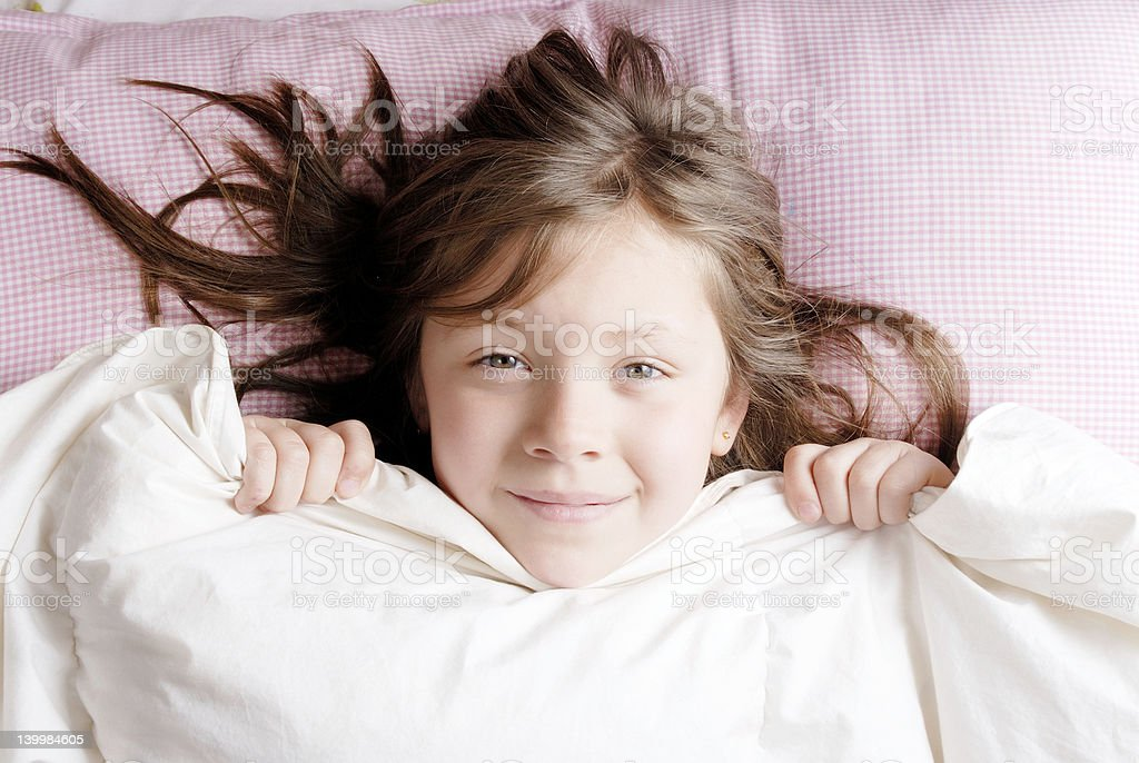 A young girl snuggled up in bed, under the duvet stock photo