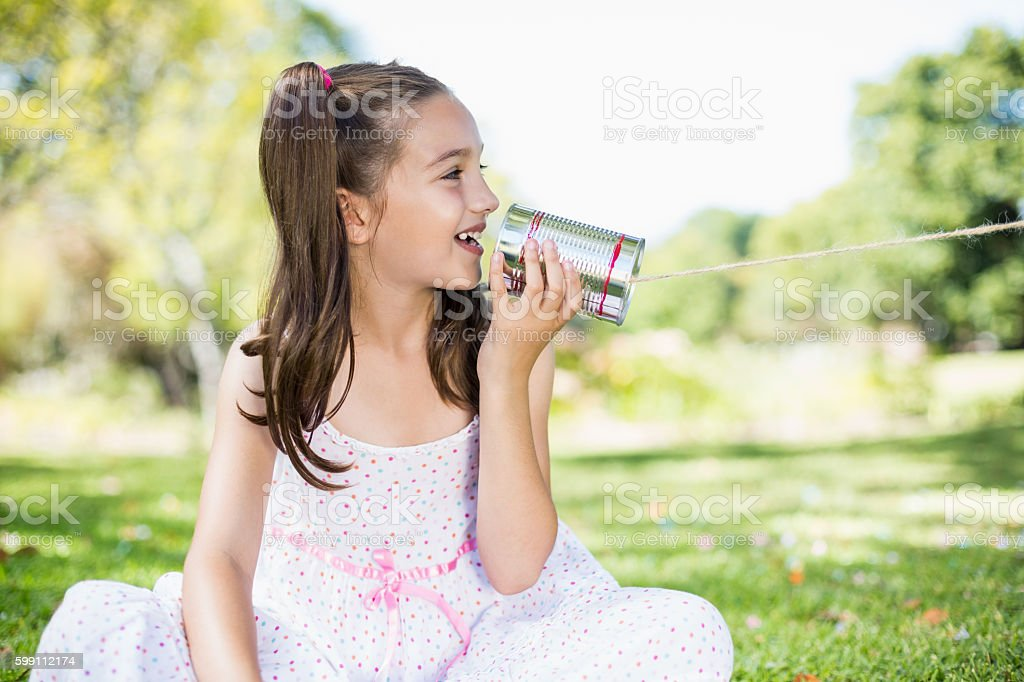 Young girl speaking through tin can phone stock photo