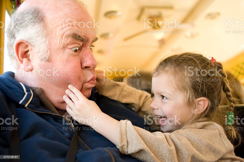 Young Girl Squeezing Grandfather's Cheeks stock photo