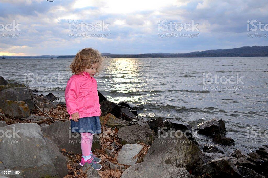 Young girl standing at lake shoreline stock photo
