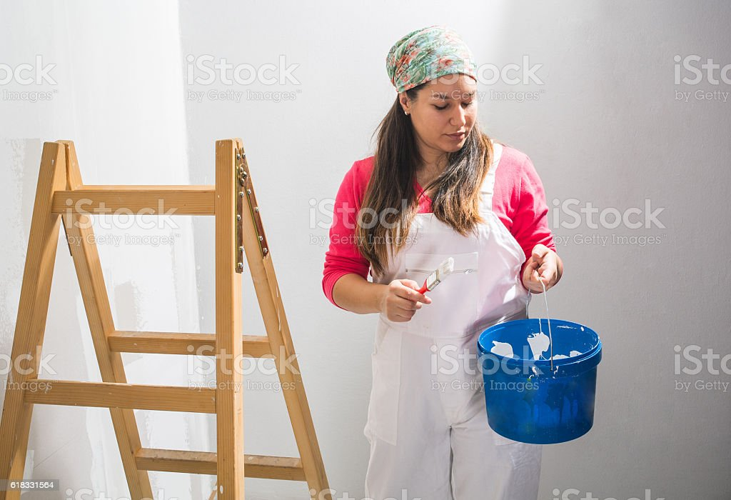 Young girl standing beside the ladders ready to paint  walls stock photo