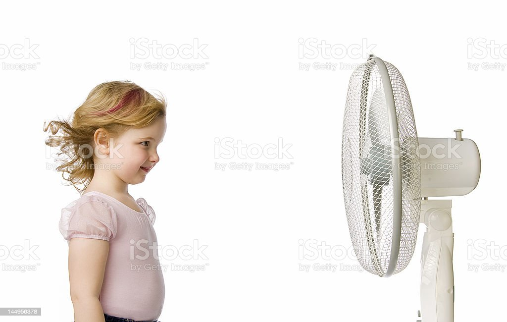 Young girl standing in front of a fan stock photo