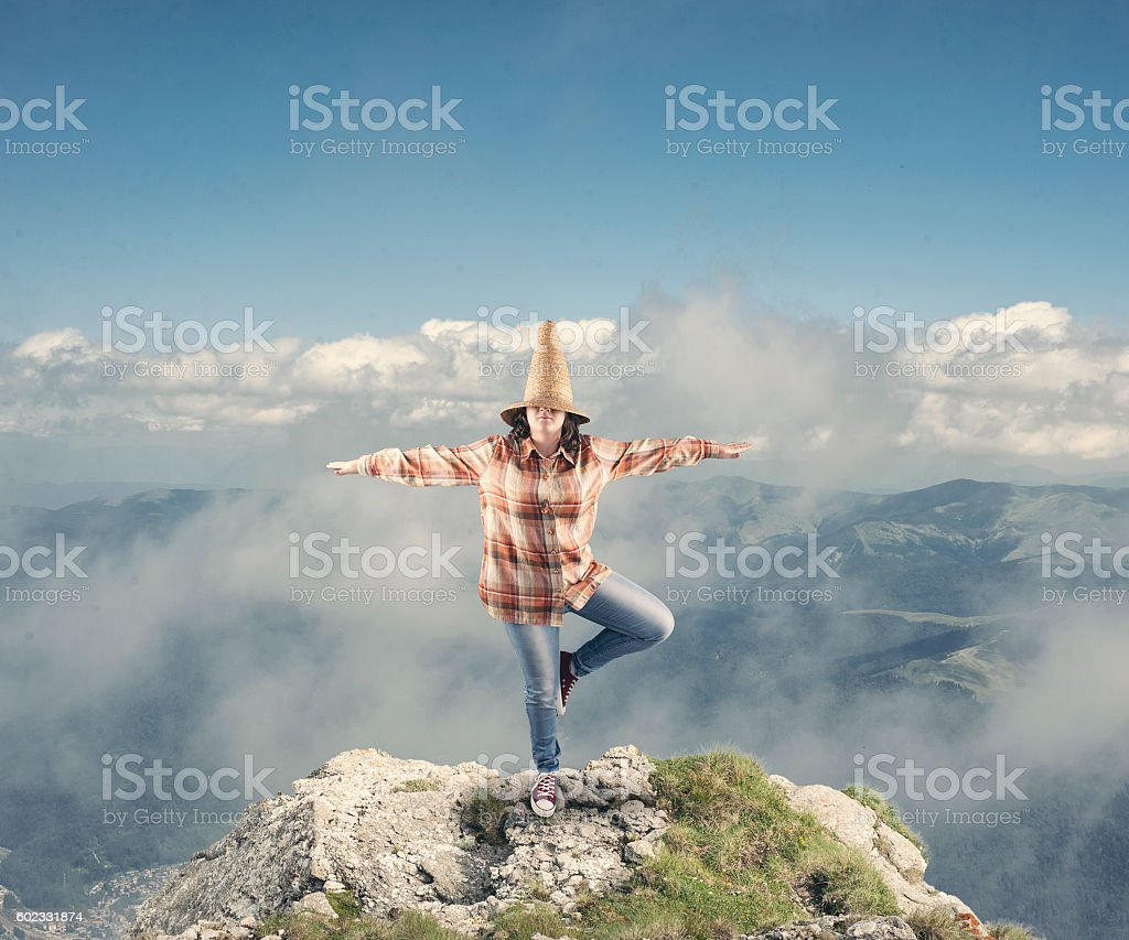 Young girl standing in one leg on the top of mountain cliff
