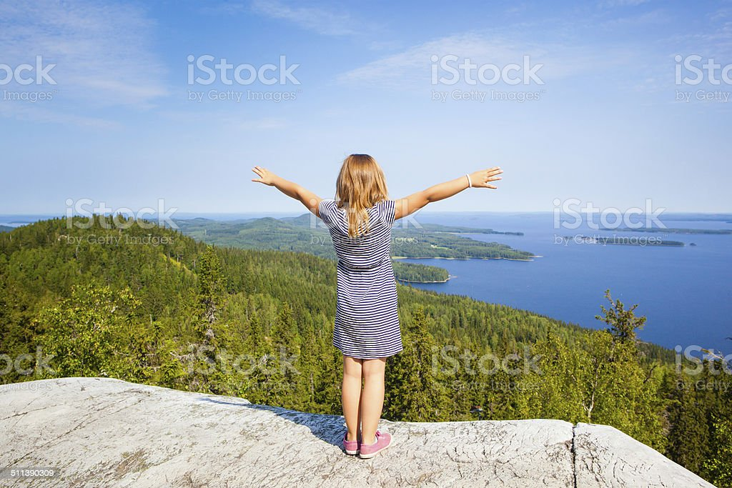 young girl standing on top of mountain royalty-free stock photo
