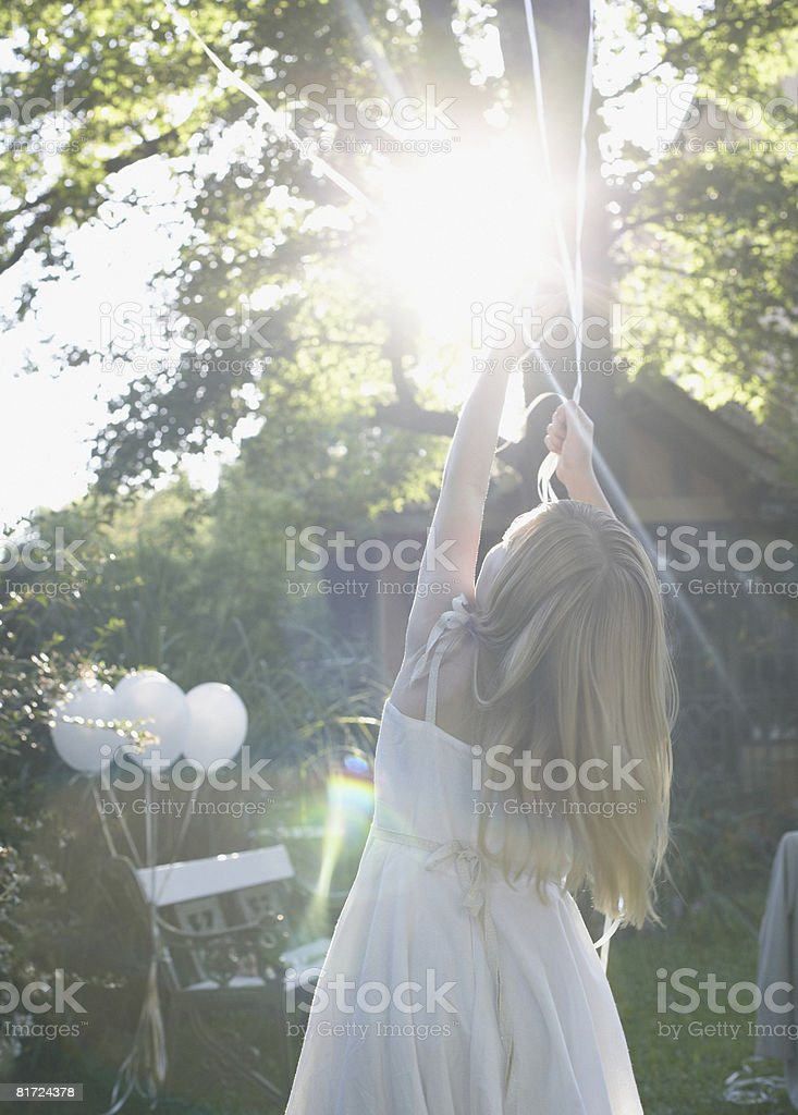 Young girl standing outdoors holding balloons stock photo