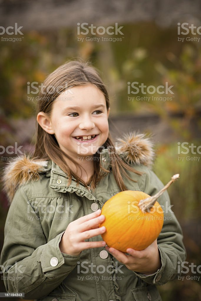 Young Girl Standing Outside Holding Pumpkin, in Autumn royalty-free stock photo
