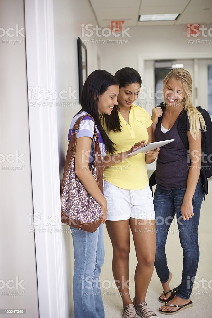 Young girl standing with college friends while holding touchpad royalty-free stock photo