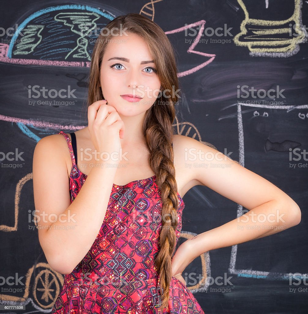 Young girl stands in front of school blackboard stock photo