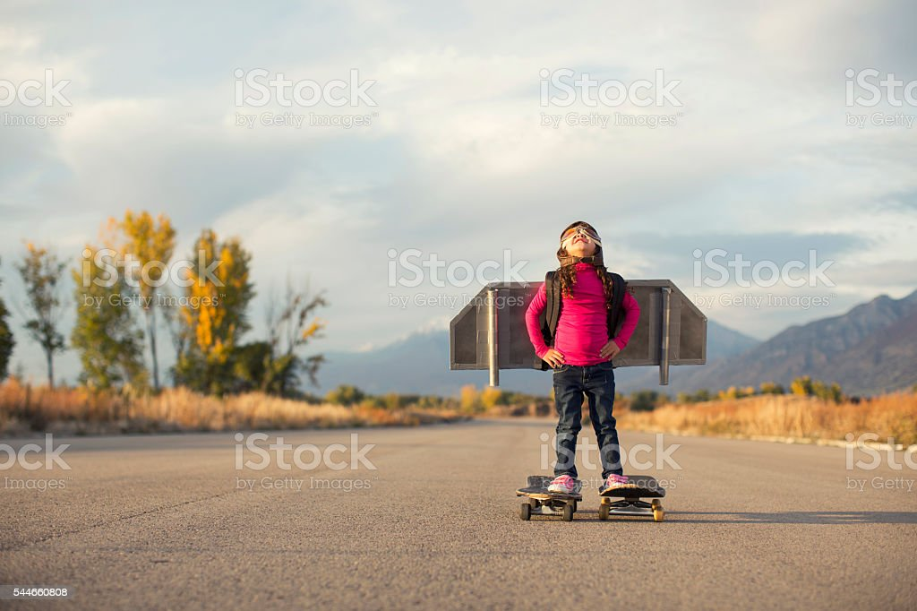 Young Girl Stands on Skateboards While Wearing a Jetpack stock photo