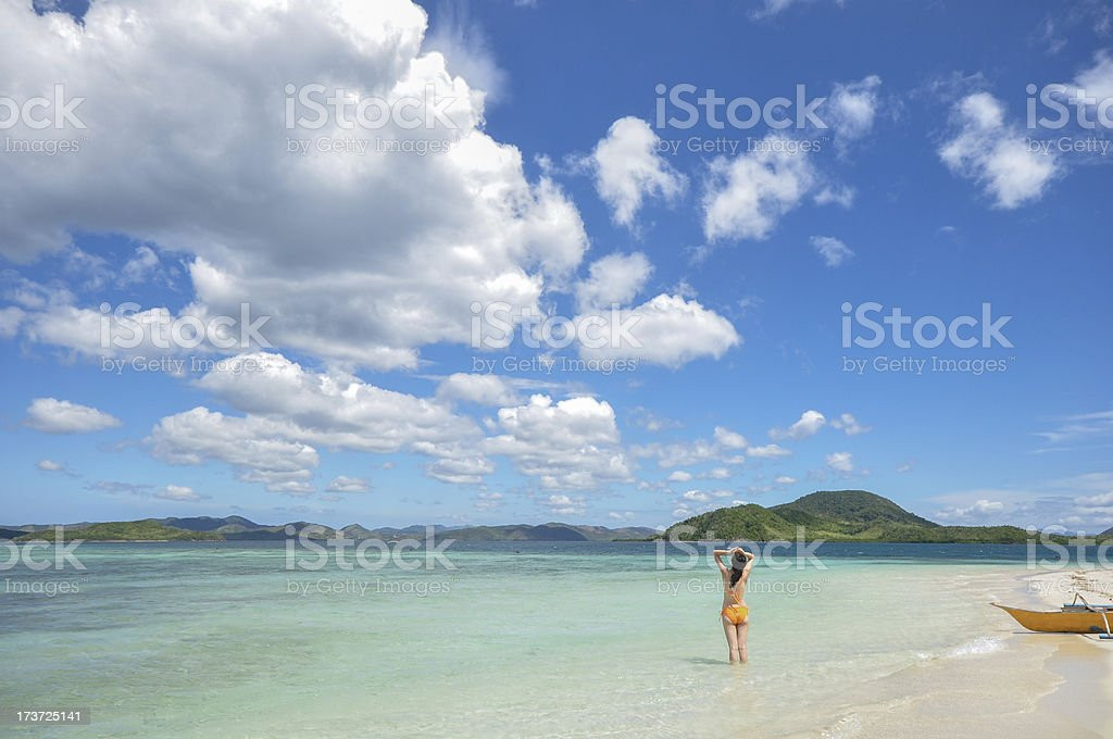young girl stands on white beach royalty-free stock photo