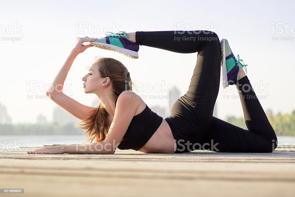 Young girl stretches at yoga pose during training workout outdoor stock photo