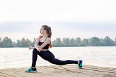 Young girl stretches her legs during training workout exercises outdoor
