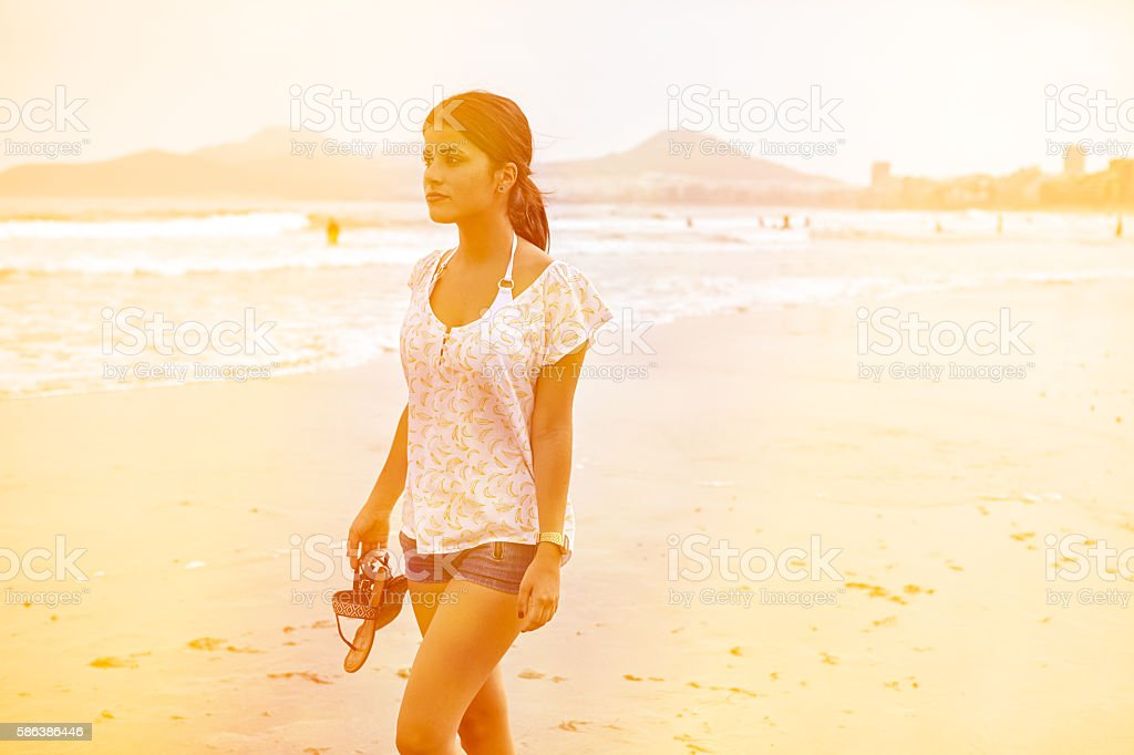 Young girl strolling on the beach stock photo