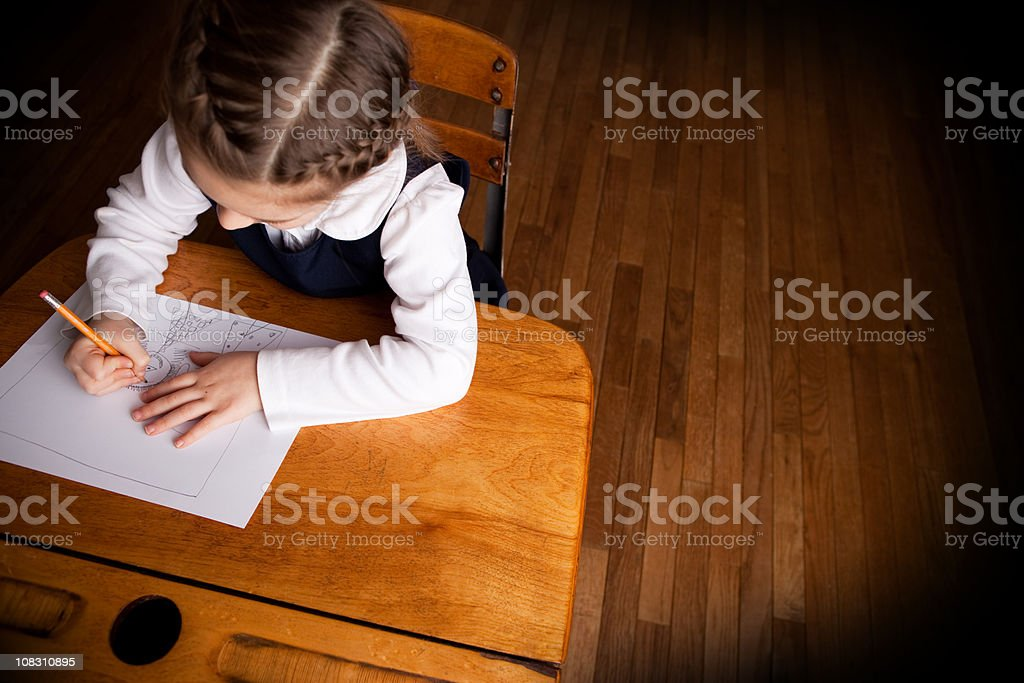 Young Girl Student Drawing Picture While Sitting in School Desk royalty-free stock photo
