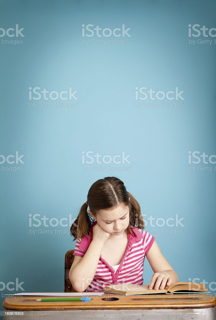 Young Girl Student Reading Book in School Desk royalty-free stock photo