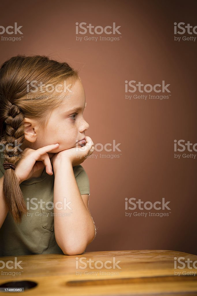 Young Girl Student Sitting and Thinking at School Desk royalty-free stock photo