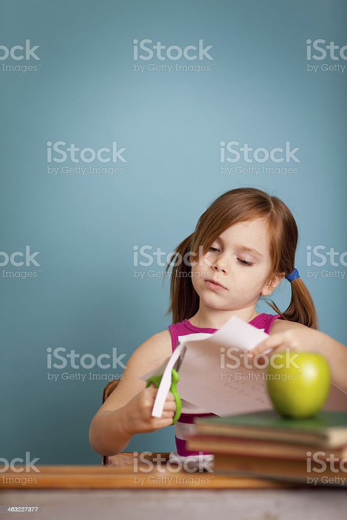 Young Girl Student Sitting at School Desk and Cutting Paper royalty-free stock photo