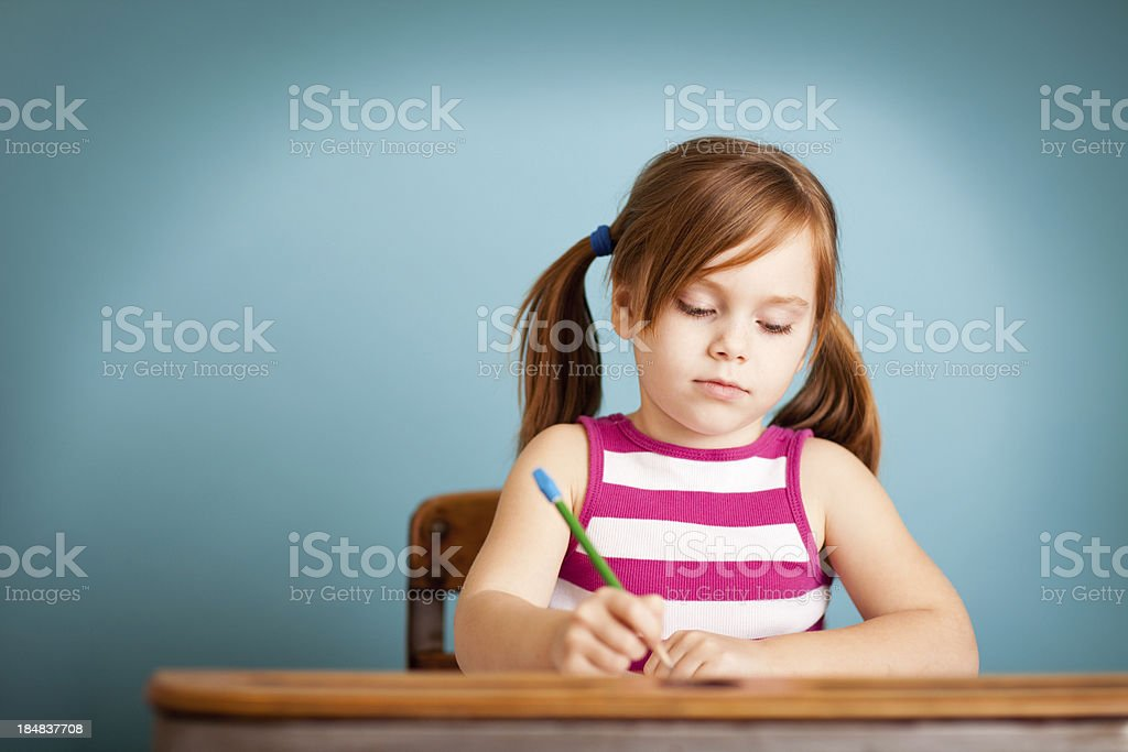 Young Girl Student Sitting at School Desk with Copy Space royalty-free stock photo