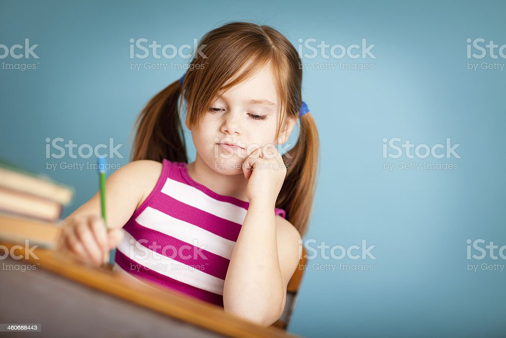 Young Girl Student Sitting at School Desk, with Copy Space royalty-free stock photo