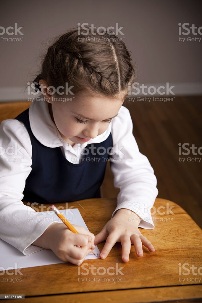 Young Girl Student Sitting in School Desk Writing the Alphabet royalty-free stock photo