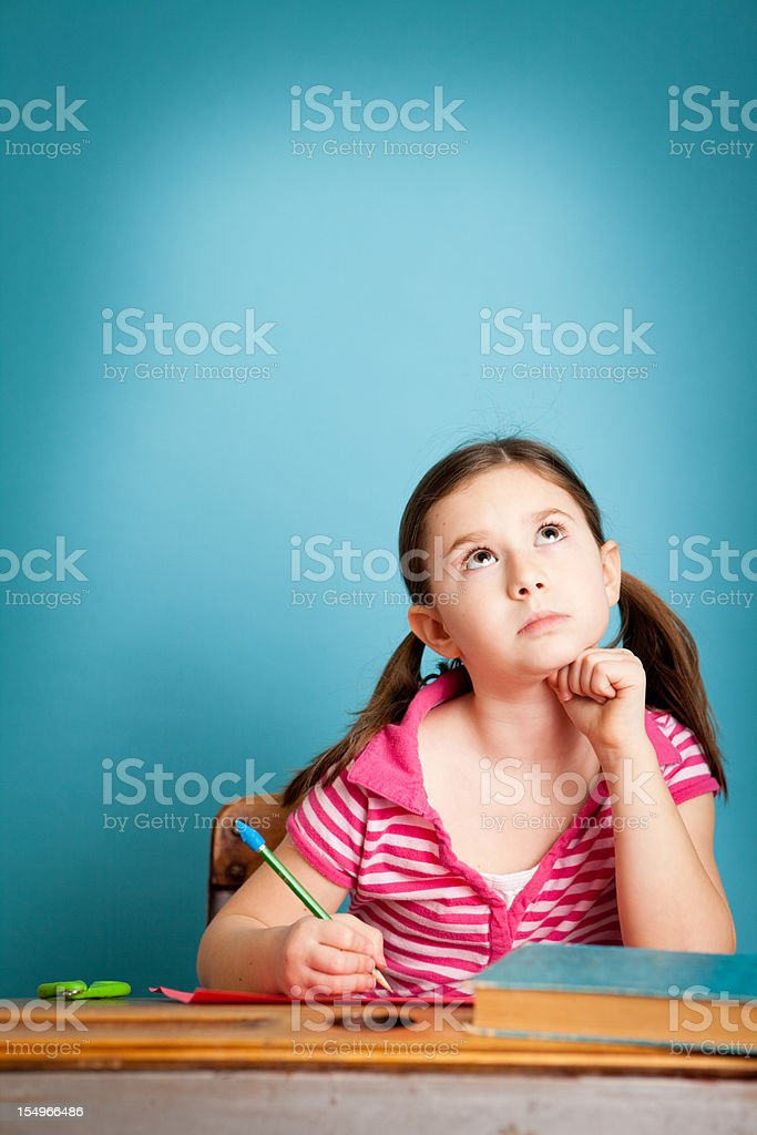 Young Girl Student Thinking and Writing at School Desk royalty-free stock photo