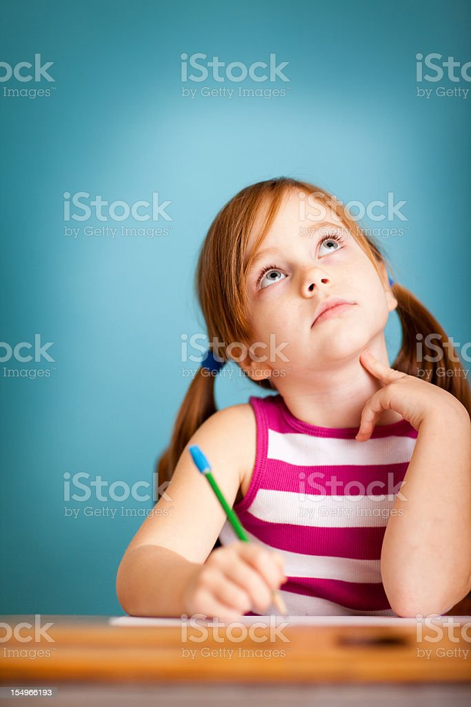 Young Girl Student Thinking in School Desk stock photo