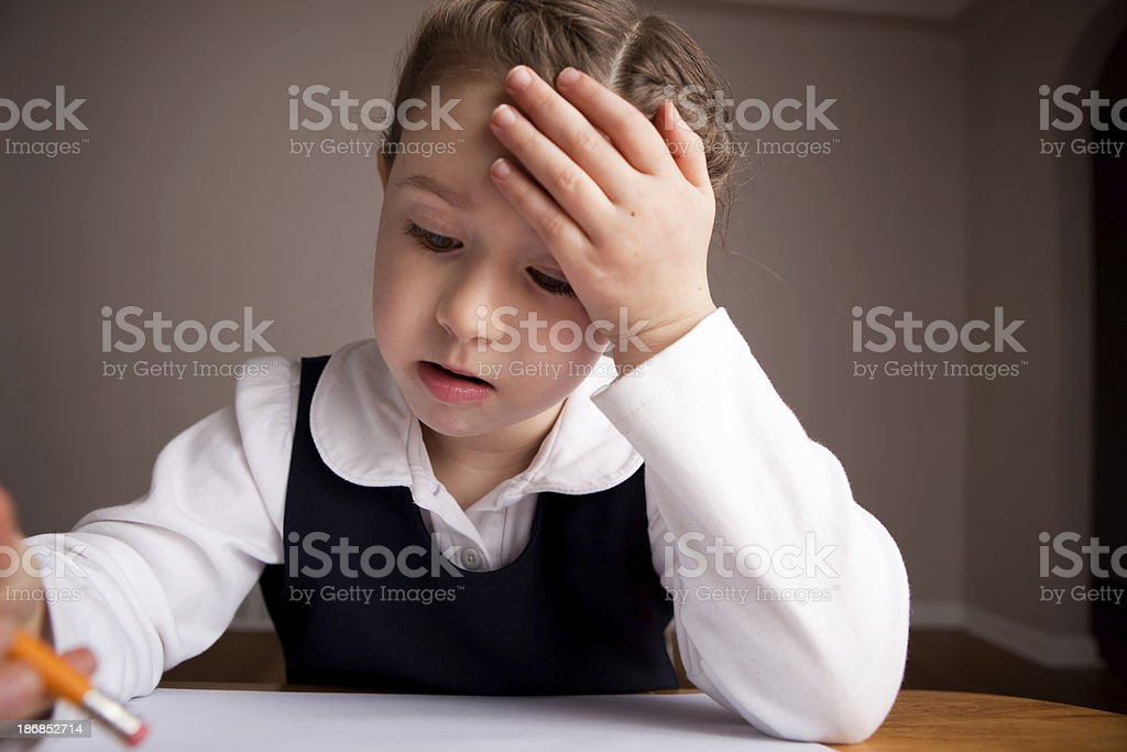Young Girl Student Thinking While Sitting in School Desk royalty-free stock photo