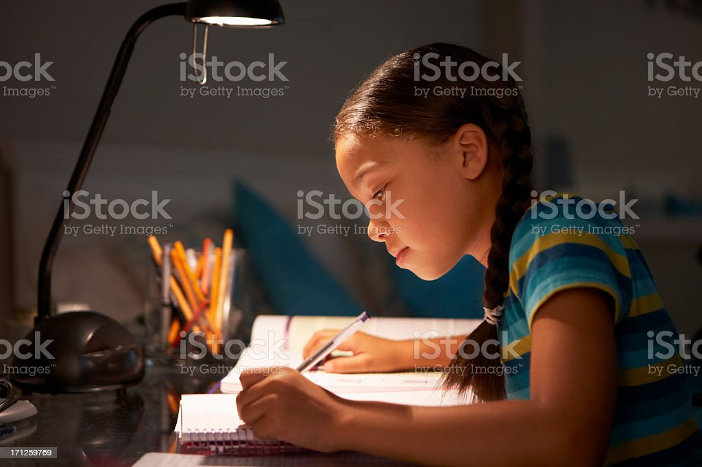Young Girl Studying At Desk In Bedroom stock photo