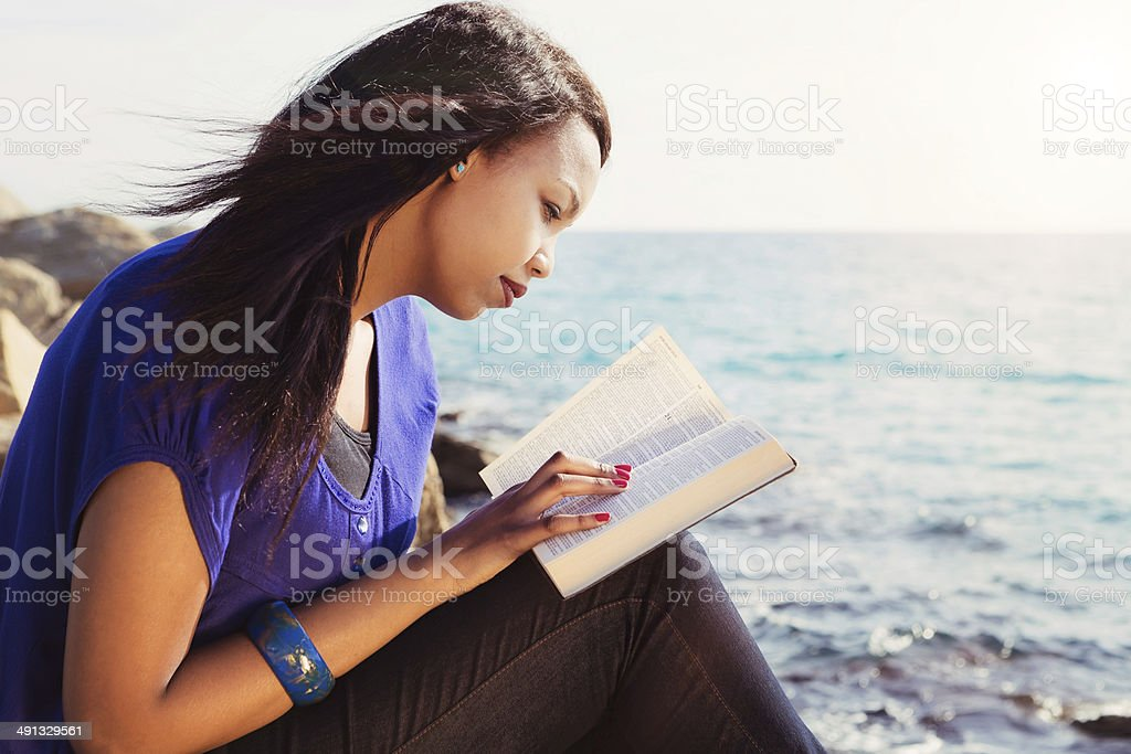 Young Girl Studying Her Bible By The Sea stock photo