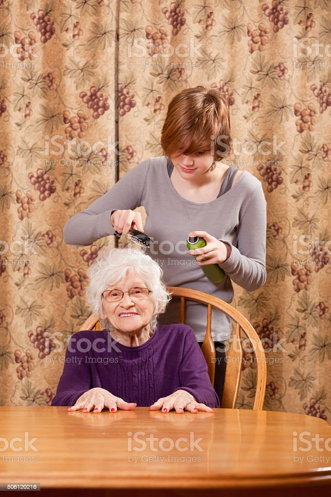 Young Girl Styling Grandmother's Hair stock photo