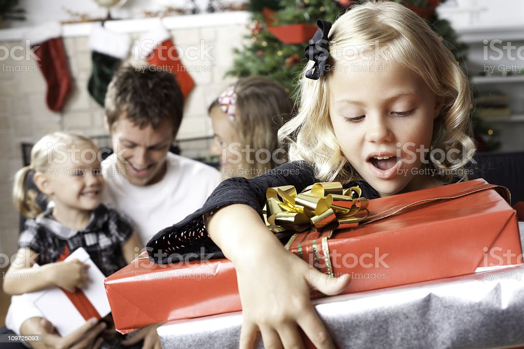 Young Girl Surprised With Christmas Presents At Home stock photo