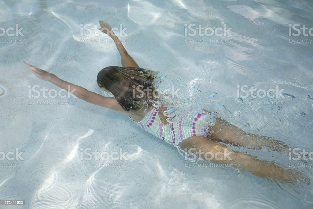 Young Girl Swims Underwater in Swimming Pool royalty-free stock photo