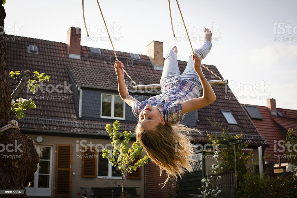 A young girl swinging in the backyard royalty-free stock photo